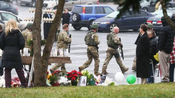 State Police officers pass a makeshift memorial as they respond to a threatening phone call that caused the evacuation of St. Rose of Lima Roman Catholic Church in Newtown during Sunday services.