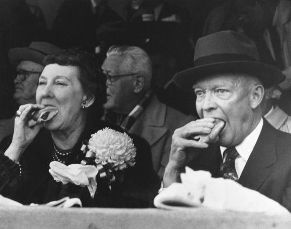 President Dwight D. Eisenhower and first lady Mamie Eisenhower eat hot dogs while watching the Army-Colgate football game in West Point, N.Y., in 1957.
