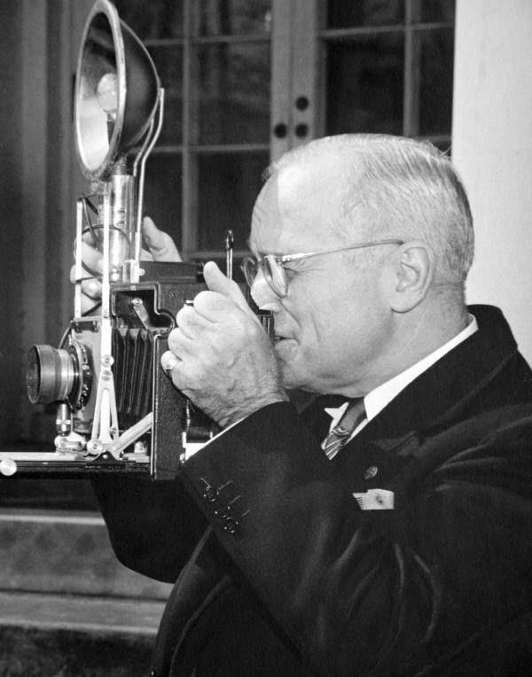President Harry S. Truman tries out a speed graphic camera given to him by members of the WHNPA during a meeting at the White House Rose Garden, 1948.