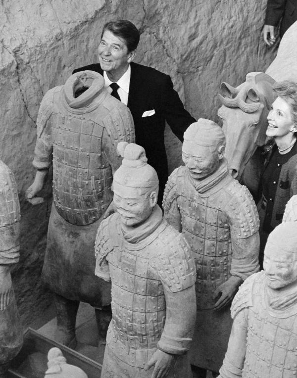 President Reagan stands behind a headless Terra Cotta Warrior as first lady Nancy Reagan looks on during a visit to the ancient historic underground army archaeological find near Xian, China, 1984.