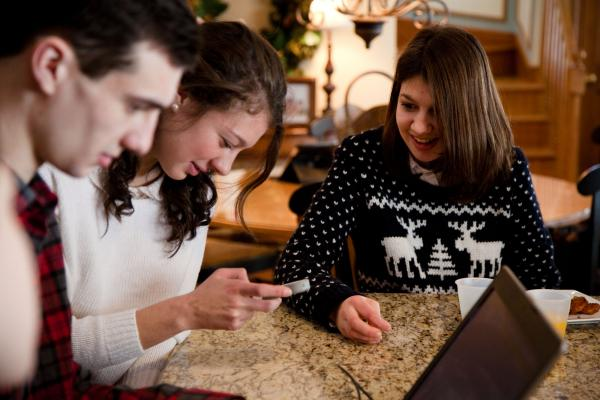 Joseph, Alexandra and Samantha Grimaldo sit around the kitchen counter in the family's home in Marlborough, Mass., playing with Samantha's voice app, though they mostly use sign language at home.