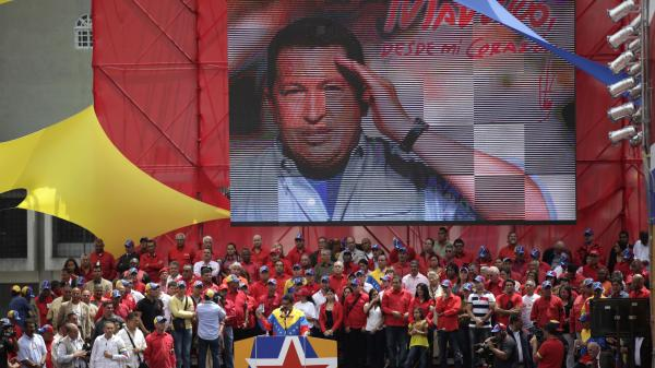 An image of late President Hugo Chavez hangs behind acting President Nicolas Maduro, as he speaks to supporters after registering his candidacy outside the national electoral council in Caracas, Venezuela, on Monday.
