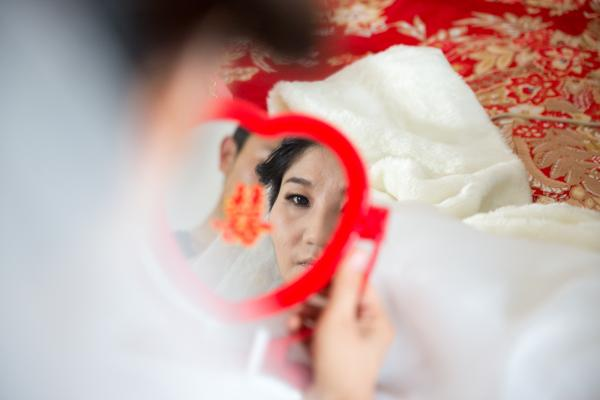 "Wang looks in a heart-shaped mirror embossed with the Chinese character <em>xi</em> — meaning ""double happiness."""