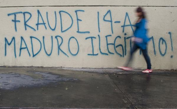 "A woman walks past a message painted on a wall in the streets of Caracas reading ""Fraud. Maduro Illegitimate."""