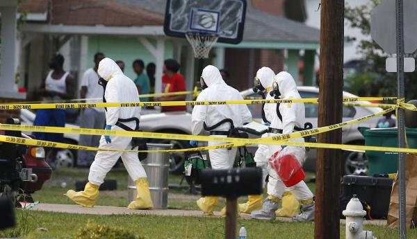 Federal authorities wearing hazmat suits walk to the home of J. Everett Dutschke on April 23, 2013 in Tupelo, Miss.