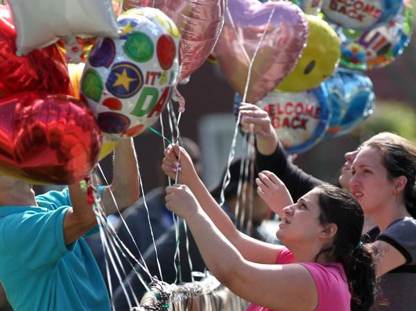 Balloons are placed Tuesday in front of the home of Gina DeJesus in Cleveland. DeJesus was found Monday, along with Amanda Berry and Michelle Knight, after disappearing nine years ago.