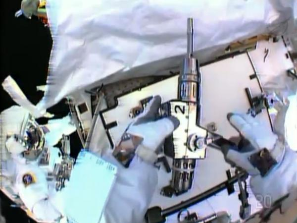 In this image made from video provided by NASA, astronaut Christopher Cassidy, foreground, holds a power wrench as he stows away a coolant pump on the International Space Station on Saturday. Thomas Marshburn is at left.