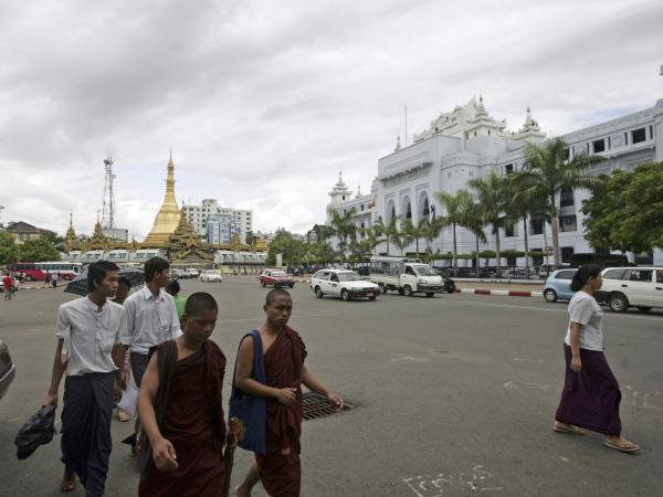 Buddhist monks and others walk across a road in downtown Yangon, Myanmar, on May 13.