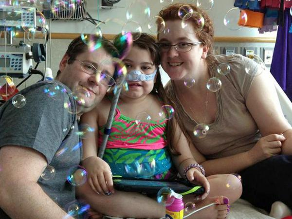 Sarah Murnaghan, center, on May 30 as she and her parents marked the 100th day of her stay in Children's Hospital of Philadelphia. Her father, Fran, is at left. Her mother, Janet, is at right.