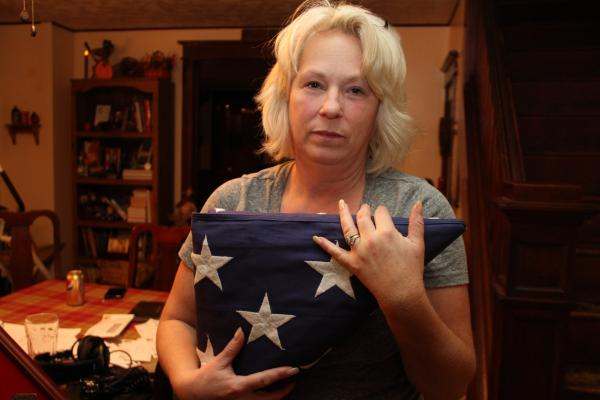 "Anna holds the flag that was draped over Nick's coffin at his memorial service. She and her husband, Michael, <a href=""http://longhaul.pro/shrine/"">have created a shrine to Nick in their dining room</a>."