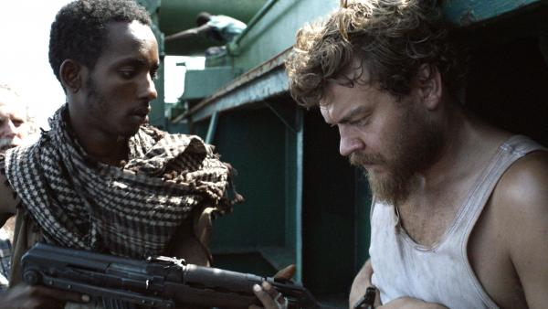 "Pilou Asbaek (right) plays ship's cook Mikkel, a new dad who desperately wishes to return to his family, but is instead forced to <a href=""javascript:NPR.Player.openPlayer(191722463,%20192797026,%20null,%20NPR.Player.Action.PLAY_NOW,%20NPR.Player.Type.STORY,%20'1')"">prepare menus at gunpoint</a> as the cargo vessel's owners negotiate for its release."
