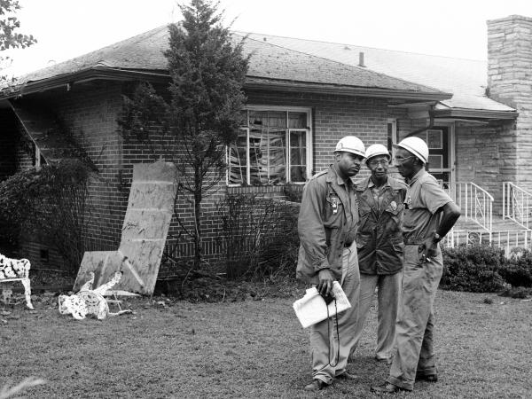 Three civil rights workers stand guard in front NAACP attorney Arthur Shores' house in Sept. 1963. The house was blasted by dynamite the night before.