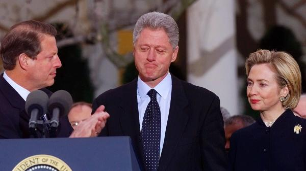 President Bill Clinton, with Vice President Al Gore and Hillary Clinton, is applauded outside the Oval Office after the House of Representatives voted to impeach him, in 1998.