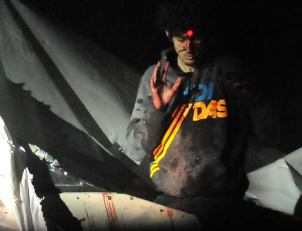 Boston bombings suspect Dzhokhar Tsarnaev emerges from a boat stored in a Watertown, Mass., backyard on April 19. The red dot of a police sharpshooter's laser sight can be seen on his forehead. This is among the images that Massachusetts State Police Sgt. Sean Murphy gave to <em>Boston Magazine</em>.