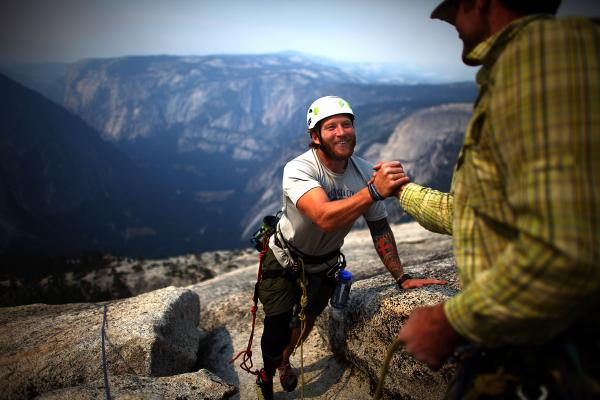 Sullens gets a handshake from Warren as he summits Half Dome.