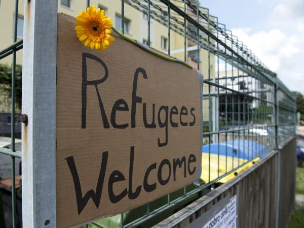 The refugees have their supporters, too. This welcome sign hangs opposite the former school that will now house asylum seekers.