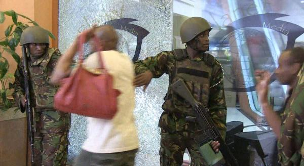 Kenyan forces help civilians flee the building on Saturday. The attackers remained inside the mall throughout the night.