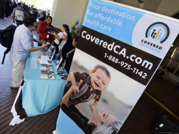 People get information on California's health exchange at a table at Union Station in Los Angeles on Tuesday, the exchange's opening day.