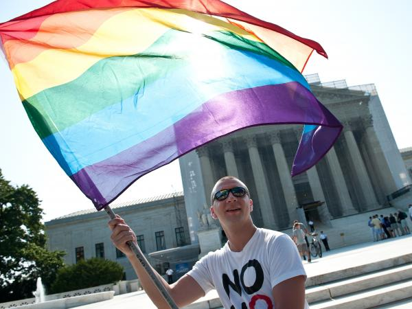 A gay rights activist waves a rainbow flag in front of the U.S. Supreme Court in June, a day before the ruling on the Defense of Marriage Act.