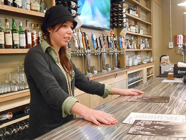 Sadie Wells helps a customer choose a beer at Skewed Brewing in Salmon Run Mall, Watertown.
