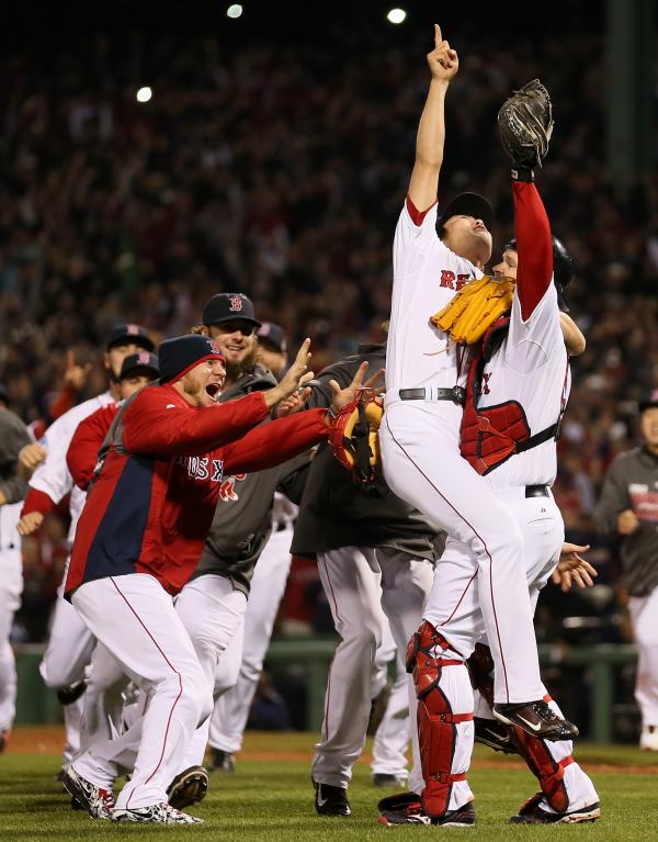 Boston Red Sox relief pitcher Koji Uehara points to the sky as he and his teammates celebrate their World Series victory Wednesday.