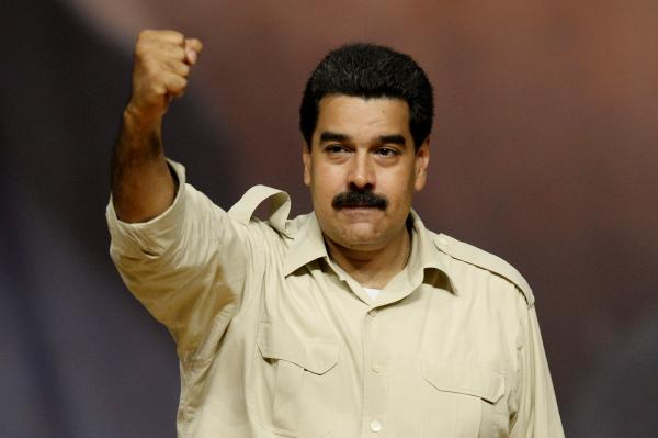 <strong>Yey Christmas:</strong> Venezuelan President Nicolas Maduro rises his clenched fist during a political meeting in Caracas, on August 7, 2013.
