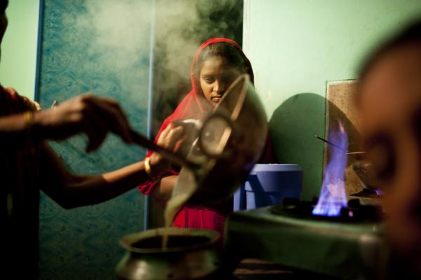 Minu cooks on the two shared burners outside the sisters' room in Chittagong.