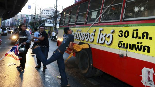 Anti-government protesters in Bangkok attack a bus that they suspect is of supporters of the current Thai government on Saturday.