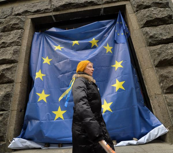 A woman walks past a giant European Union flag hung on the gates of the Ukrainian Cabinet of Ministers building in Kiev on Monday.