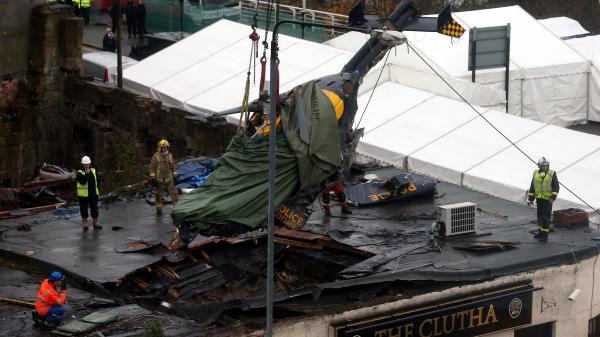 Scottish Fire and Rescue services look on at the helicopter being lifted from the scene Monday following the crash at the Clutha Bar in Glasgow, Scotland.