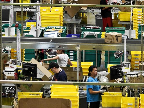 Workers pull merchandise as it arrives at the Amazon.com's 1.2 million square foot fulfillment center in Phoenix on Nov. 26. Americans clicked away on their computers and smartphones for deals on Cyber Monday, which is expected to be the biggest online shopping day in history.