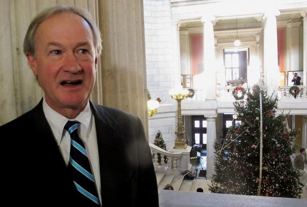 "Rhode Island Gov. Lincoln Chafee speaks with reporters in November of 2012, during the lighting the Statehouse Christmas tree. Chafee announced the ceremony 30 minutes ahead of time to avoid what he called the ""chaos"" of 2011's lighting, which was protested by people angered by Chafee's decision to call the Statehouse tree a ""holiday"" tree."