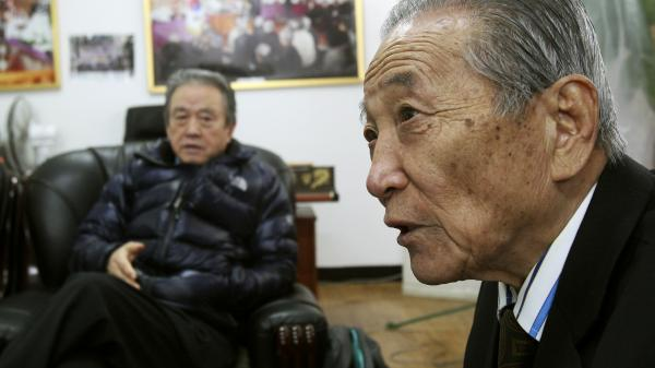 Park Boo Seo (right), a former member of the Korean Kuwol partisan unit, speaks about Merrill Newman, an American tourist detained in North Korea. Newman supervised the group during the Korean War.
