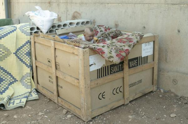 A one-year old Syrian refugee in his bed and play pen in Tripoli, Lebanon. His family fled Syria just after he was born. He spends most of his time in this box which is his bed, play pen, refuge. This crate resides on the grounds of an active slaughter house where his family now lives. (Elena Dorfman)