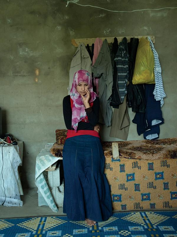 Iman, 19, from Homs, is married but her husband stayed in Syria. She last saw him four months ago. He can't leave the country because he is of army age and, if caught crossing a checkpoint, will be sent to fight for the regime. She misses him by her side and dreams of living a normal life back in Syria, in their own home. She said that she cleans the room she shares in a collective shelter obsessively, because it is the only thing she can do, the only control she has. (Elena Dorfman)