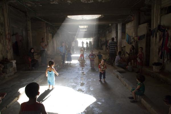 In Akbiya, Lebanon, these dark, underground streets -- former storage units -- are home to more than 200 Syrian refugees. Children play in the dirty water and in the darkness. (Elena Dorfman)