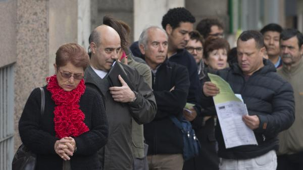 People line up outside a government unemployment office in Madrid on Oct. 5. Spain has an unemployment rate of 26 percent.