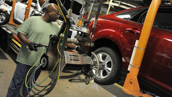 An auto worker tightens bolts on the wheel of a Focus at a Ford plant in Wayne, Mich. Reports this week showed increases in auto sales and manufacturing jobs.