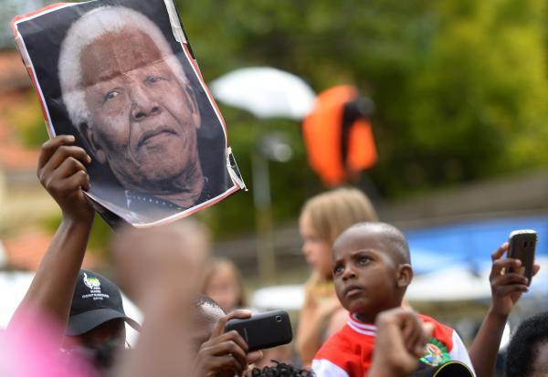 A man holds a portrait of Nelson Mandela outside his home in Houghton, Johannesburg, on Sunday.