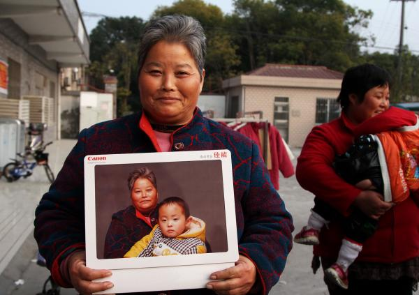 Zheng Jinrong poses with a portrait of herself and her grandson in a migrant village in Shanghai. She received the photographs as part of a global event to provide high-quality portraits for people who otherwise can't afford them.