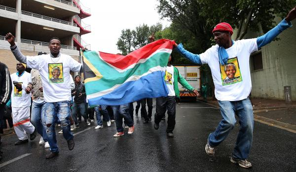 People holding a South African flag sing as they arrive at Ellis Park in Johannesburg, South Africa, to watch a telecast of the Nelson Mandela memorial service on Tuesday.