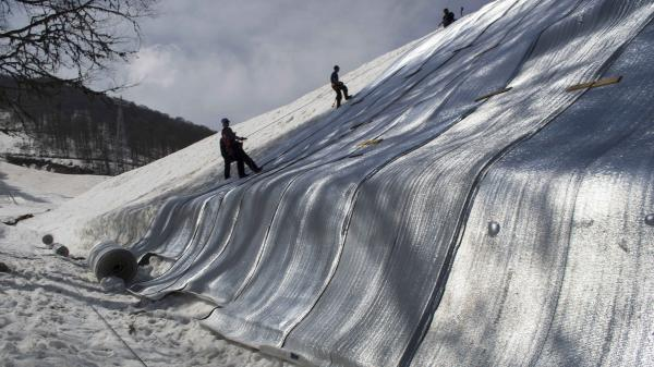 Ski resort employees in Sochi, Russia, scale down a pile of snow covered by insulated fabric.