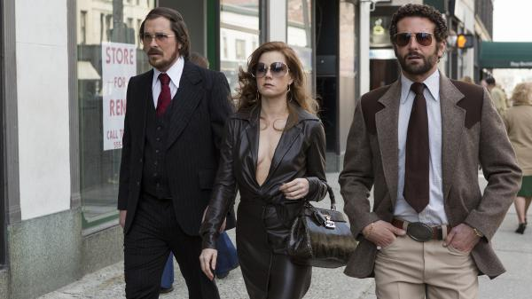 A '70s con-artist couple (Christian Bale and Amy Adams) are forced to team up with an FBI agent (Bradley Cooper, right) in <em>American Hustle,</em> inspired by a real-life sting targeting corrupt politicians.