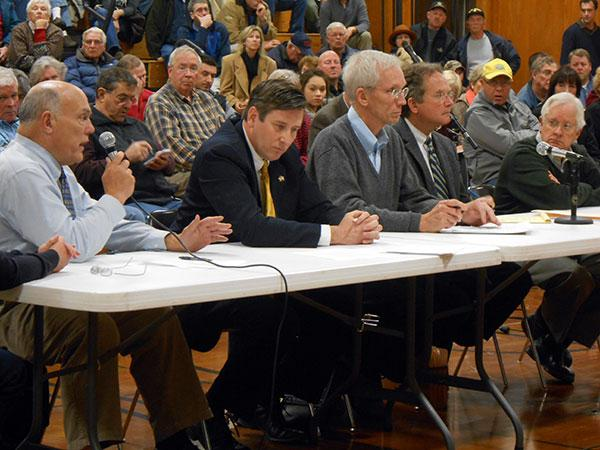 Cape Vincent Town Councilman Brooks Bragdon addresses state officials about BP's proposed wind farm at a meeting Monday night at Cape Vincent Elementary School. He's flanked by other town officials.