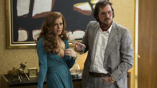 Amy Adams and Christian Bale star as a couple of con artists in David O. Russell's <em>American Hustle</em>.
