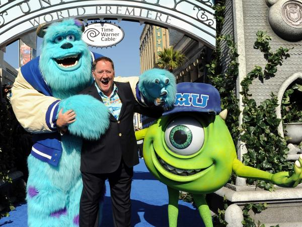 John Lasseter, flanked by Mike and Sulley, at the premier of <em>Monsters University</em> in June. Lasseter's career took him from Disney to Pixar back to Disney again.