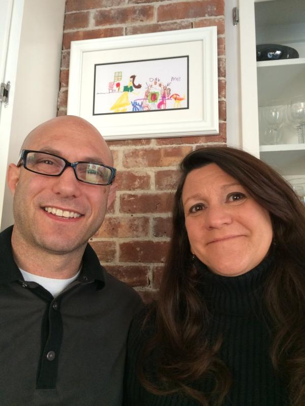 "Jeremy Richman and Jennifer Hensel pose at their home with artwork from their daughter, Avielle. Richman says his daughter ""was very happy and wanted everyone else to be, too."""