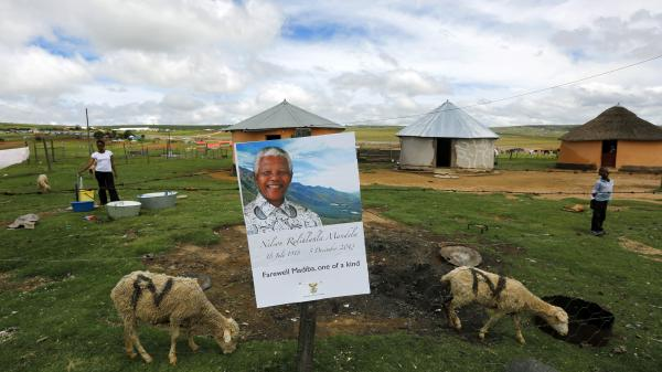 A mother and her son stand in their garden behind a fence at the perimeter of Nelson Mandela's property in Qunu, South Africa, as funeral preparations continue Friday. Mandela will be buried Sunday in the small, rural village that was his boyhood home.