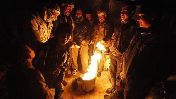 Syrian refugees from the town of Qara gather around a fire to keep themselves warm in a refugee camp in the Lebanese border town of Arsal on Thursday.
