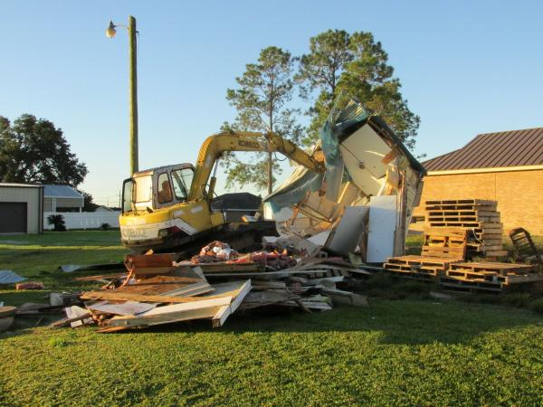 A bulldozer tosses the old bathroom at Our Lady of Peace Catholic church.